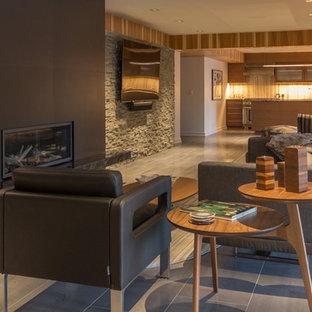 Exemple d'un très grand sous-sol rétro donnant sur l'extérieur avec un mur gris, un sol en carrelage de porcelaine, une cheminée standard, un manteau de cheminée en carrelage et un sol gris.
