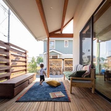 屋根が深くかかったウッドデッキ。多少の雨でも心地よく過ごせます。手造りの目隠しフェンスやベンチ、ソファ。子どもたちはのびのび過ごしています。