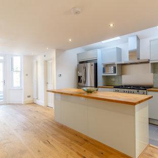 ロンドンの大きいコンテンポラリースタイルのおしゃれなキッチン (ドロップインシンク、フラットパネル扉のキャビネット、ターコイズのキャビネット、木材カウンター、緑のキッチンパネル、セラミックタイルのキッチンパネル、シルバーの調理設備の、セメントタイルの床、グレーの床、茶色いキッチンカウンター) の写真