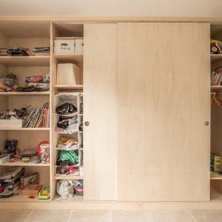 Inredning av ett modernt mellanstort könsneutralt barnrum för 4-10-åringar, med flerfärgade väggar, travertin golv och beiget golv