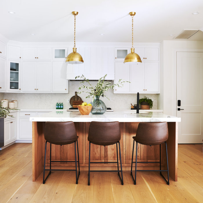 Eat-in kitchen - transitional medium tone wood floor, brown floor and vaulted ceiling eat-in kitchen idea in Los Angeles with stainless steel appliances and an island