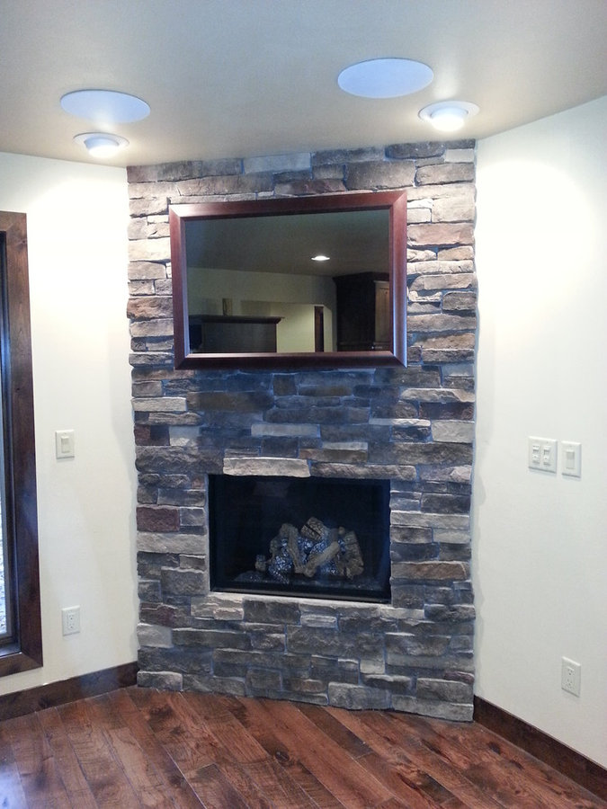 Seura Mirrored TV Installation Above a Stacked Stone Fireplace
