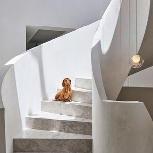 Идея дизайна: огромная винтовая лестница в стиле модернизм с ступенями из известняка и подступенками из известняка