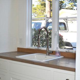 Idéer för ett mellanstort lantligt brun parallellt grovkök, med en nedsänkt diskho, luckor med infälld panel, vita skåp, träbänkskiva, brunt stänkskydd, stänkskydd i trä, vita väggar, klinkergolv i terrakotta, en tvättmaskin och torktumlare bredvid varandra och flerfärgat golv
