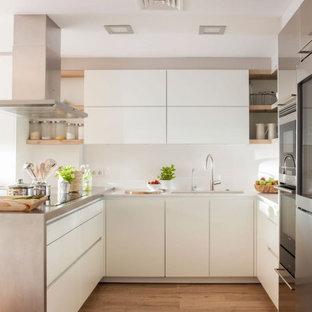 Foto de cocina en U, actual, con fregadero bajoencimera, armarios con paneles lisos, puertas de armario blancas, electrodomésticos de acero inoxidable, suelo de madera clara, península, suelo beige y encimeras grises