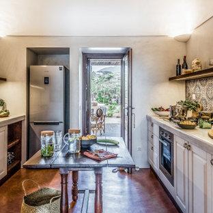 Immagine di una cucina parallela mediterranea chiusa con lavello sottopiano, ante con bugna sagomata, ante bianche, paraspruzzi multicolore, elettrodomestici in acciaio inossidabile, pavimento in cemento, 2 o più isole, pavimento marrone e top grigio