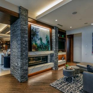 Großes Modernes Arbeitszimmer mit grauer Wandfarbe, Porzellan-Bodenfliesen, Tunnelkamin, Kaminumrandung aus gestapelten Steinen, Einbau-Schreibtisch und braunem Boden in Omaha
