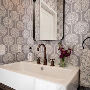 Cette image montre un petit WC et toilettes rustique avec un placard en trompe-l'oeil, des portes de placard en bois sombre, un WC séparé, un carrelage marron, des carreaux en terre cuite, un mur gris, un sol en brique et un lavabo intégré.