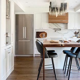 トロントの中くらいのトランジショナルスタイルのおしゃれなキッチン (アンダーカウンターシンク、白いキャビネット、クオーツストーンカウンター、白いキッチンパネル、クオーツストーンのキッチンパネル、シルバーの調理設備、無垢フローリング、白いキッチンカウンター、シェーカースタイル扉のキャビネット、茶色い床) の写真
