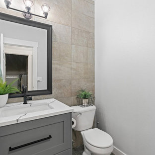 Photo of a small modern 3/4 bathroom in Seattle with beaded inset cabinets, grey cabinets, a one-piece toilet, beige tile, ceramic tile, grey walls, cement tiles, an undermount sink, marble benchtops, black floor, white benchtops, a single vanity, a freestanding vanity and wallpaper.