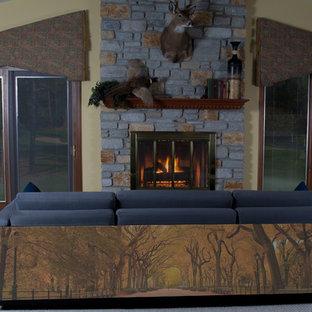 シンシナティの中サイズのモダンスタイルのおしゃれな独立型ファミリールーム (ライブラリー、黄色い壁、カーペット敷き、標準型暖炉、石材の暖炉まわり、テレビなし、グレーの床) の写真