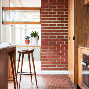 Inspiration for a midcentury kitchen in Melbourne with marble benchtops, brick floors, red floor and yellow benchtop.