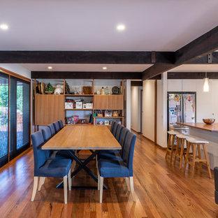 Foto på en liten 60 tals matplats med öppen planlösning, med vita väggar och brunt golv