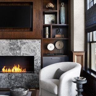 シカゴの広いトランジショナルスタイルのおしゃれな書斎 (グレーの壁、濃色無垢フローリング、横長型暖炉、石材の暖炉まわり、自立型机、茶色い床、三角天井、パネル壁) の写真