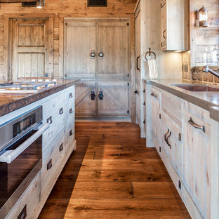 Inspiration for a mid-sized country l-shaped kitchen pantry in San Francisco with a single-bowl sink, flat-panel cabinets, beige cabinets, copper benchtops, multi-coloured splashback, porcelain splashback, stainless steel appliances, medium hardwood floors and with island.