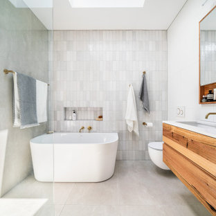 This is an example of a small contemporary master bathroom in Melbourne with furniture-like cabinets, medium wood cabinets, a freestanding tub, an open shower, a wall-mount toilet, gray tile, mosaic tile, white walls, porcelain floors, an undermount sink, solid surface benchtops, grey floor, an open shower, white benchtops, a shower seat, a single vanity and a floating vanity.