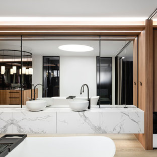 Expansive contemporary master bathroom in Sydney with a freestanding tub, a double shower, medium hardwood floors, a vessel sink, marble benchtops, a hinged shower door, an enclosed toilet, a double vanity and a floating vanity.