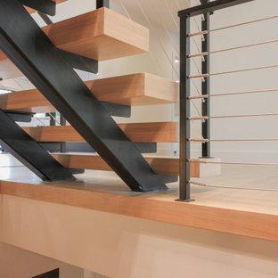 Idee per una grande scala sospesa boho chic con pedata in legno, parapetto in metallo e pareti in mattoni