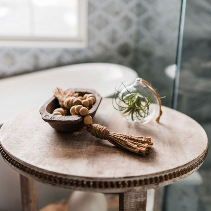 The details matter.  Adding a small table adjacent to the tub makes a place for a glass of wine, bath salts, a touch of greenery.  Air plants do really well in a bathroom.  This little table brings wa