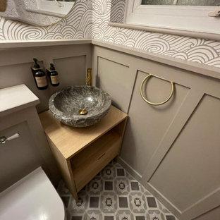 На фото: маленький туалет в классическом стиле с открытыми фасадами, светлыми деревянными фасадами, унитазом-моноблоком, полом из керамической плитки, столешницей из дерева, серым полом, напольной тумбой, сводчатым потолком и панелями на части стены