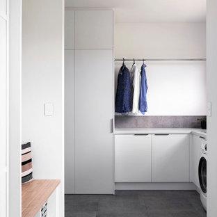 Exempel på en mellanstor modern grå l-formad grått tvättstuga enbart för tvätt, med en undermonterad diskho, släta luckor, grå skåp, bänkskiva i terrazo, grått stänkskydd, stänkskydd i keramik, vita väggar, klinkergolv i keramik, en tvättmaskin och torktumlare bredvid varandra och grått golv