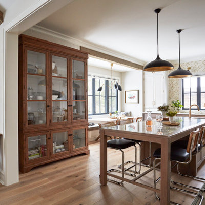 Inspiration for an eclectic light wood floor and brown floor eat-in kitchen remodel in Chicago with recessed-panel cabinets, white cabinets, quartzite countertops, white backsplash, stainless steel appliances, an island and yellow countertops
