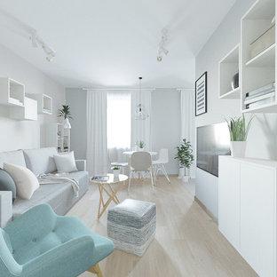 Foto de salón abierto, escandinavo, pequeño, con paredes grises, suelo laminado, televisor colgado en la pared y suelo rosa