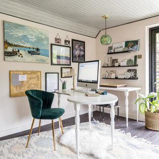 Klassisches Arbeitszimmer mit beiger Wandfarbe, dunklem Holzboden, freistehendem Schreibtisch, braunem Boden und Holzdielendecke in Surrey