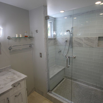 Glass and Carrara Marble shower with linear drain and recycle glass pebble floor