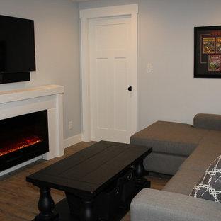 Imagen de sala de estar cerrada, costera, pequeña, con paredes grises, suelo vinílico, chimenea lineal, marco de chimenea de madera y televisor colgado en la pared