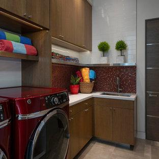 Idéer för att renovera ett stort funkis vit parallellt vitt grovkök, med en undermonterad diskho, släta luckor, skåp i mellenmörkt trä, bänkskiva i kvartsit, rött stänkskydd, stänkskydd i mosaik, vita väggar, klinkergolv i porslin, en tvättmaskin och torktumlare bredvid varandra och grått golv