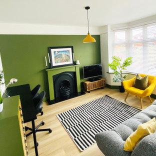Mittelgroßes Modernes Arbeitszimmer mit grüner Wandfarbe, Vinylboden, Kaminumrandung aus Holz, freistehendem Schreibtisch und beigem Boden in Dorset