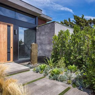 Imagen de fachada de casa gris, contemporánea, grande, de dos plantas, con revestimiento de hormigón, tejado plano y techo verde