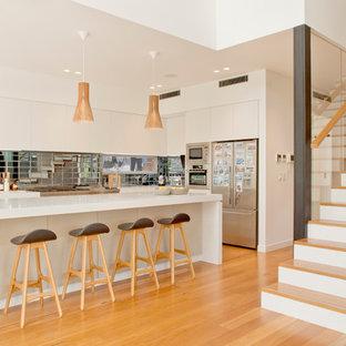 Foto di una cucina parallela minimal di medie dimensioni con ante lisce, ante bianche, elettrodomestici in acciaio inossidabile, isola e paraspruzzi con piastrelle di metallo
