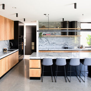 Large industrial galley kitchen pantry in Melbourne with an integrated sink, recessed-panel cabinets, black cabinets, granite benchtops, grey splashback, granite splashback, black appliances, concrete floors, with island, grey floor and grey benchtop.