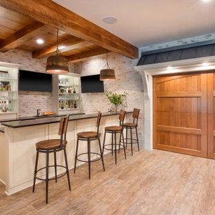 Idées déco pour un grand sous-sol campagne semi-enterré avec un bar de salon, un sol en vinyl, une cheminée standard, un manteau de cheminée en pierre, un plafond en lambris de bois et un mur en parement de brique.
