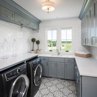 Idee per una sala lavanderia tradizionale con ante in stile shaker, ante grigie, top in vetro, paraspruzzi bianco, lavatrice e asciugatrice affiancate, pavimento multicolore e top bianco