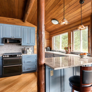 Large country l-shaped open plan kitchen in Seattle with an undermount sink, raised-panel cabinets, blue cabinets, quartz benchtops, blue splashback, glass tile splashback, stainless steel appliances, bamboo floors, a peninsula, brown floor, white benchtop and wood.