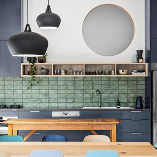 Design ideas for a mid-sized contemporary single-wall open plan kitchen in Melbourne with a drop-in sink, flat-panel cabinets, grey cabinets, solid surface benchtops, green splashback, ceramic splashback, stainless steel appliances, medium hardwood floors, with island and grey benchtop.