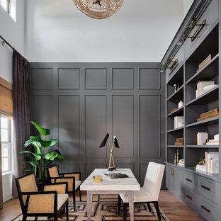 Mittelgroßes Klassisches Arbeitszimmer mit Arbeitsplatz, grauer Wandfarbe, hellem Holzboden, freistehendem Schreibtisch, grauem Boden, Tapetendecke und vertäfelten Wänden in Austin