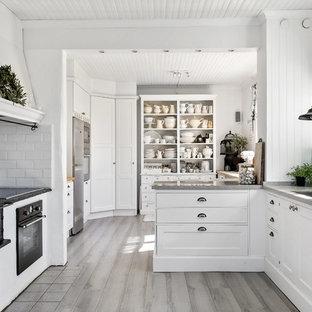 Ejemplo de cocina comedor de galera, romántica, de tamaño medio, con armarios con paneles empotrados, suelo de madera clara y península