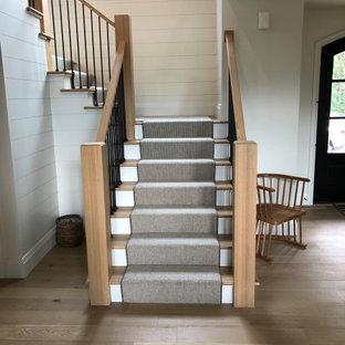 Свежая идея для дизайна: угловая лестница в стиле кантри с ступенями с ковровым покрытием, деревянными перилами и стенами из вагонки - отличное фото интерьера