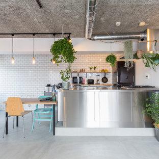 他の地域の広いインダストリアルスタイルのおしゃれなキッチン (一体型シンク、インセット扉のキャビネット、ステンレスキャビネット、ステンレスカウンター、シルバーの調理設備、コンクリートの床、板張り天井) の写真