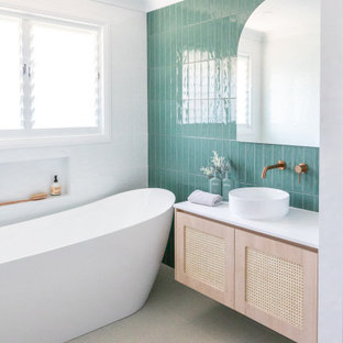 Photo of a mid-sized beach style master bathroom in Other with light wood cabinets, a freestanding tub, an open shower, multi-coloured tile, ceramic tile, multi-coloured walls, porcelain floors, a vessel sink, solid surface benchtops, white floor, an open shower, white benchtops, a niche, a single vanity and a floating vanity.