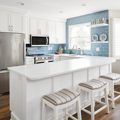 Example of a small beach style galley eat-in kitchen design in Other with white cabinets, stainless steel appliances and a peninsula