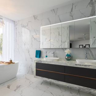 Inspiration for a contemporary bathroom in Gold Coast - Tweed with a freestanding tub, white tile, white walls, marble benchtops, black floor, a double vanity and a floating vanity.
