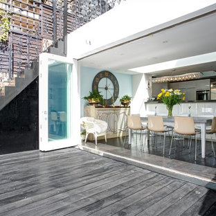 This is an example of a contemporary open plan kitchen in London with dark hardwood flooring.