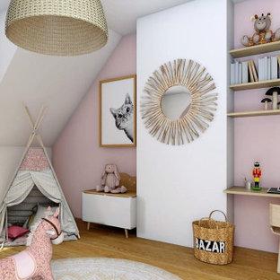 Ejemplo de habitación de bebé niña escandinava, de tamaño medio, con paredes rosas y suelo de madera clara
