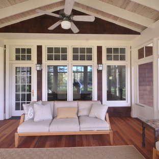 This is an example of a large craftsman screened-in back porch design in Boston with decking and a roof extension.