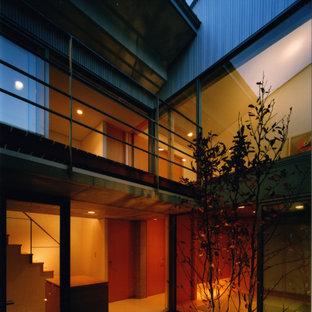 Ispirazione per un patio o portico moderno davanti casa con piastrelle